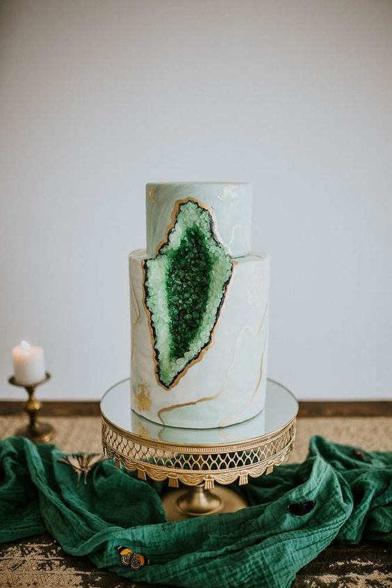 a marble wedding cake with ombre green geode decor and gilded edges