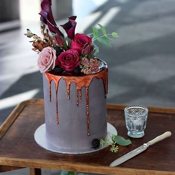 a matte grey wedding cake with copepr drpping, bold blooms and blackberries on top