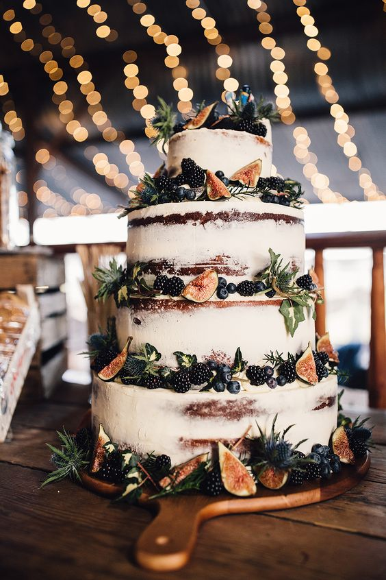 a semi naked wedding cake with blueberries, figs, blackberries and thistles and foliage