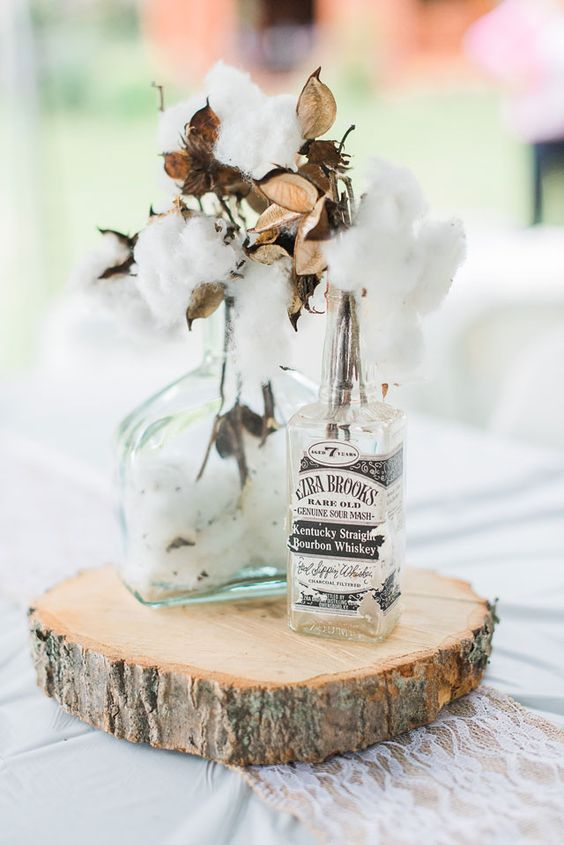 a wedding centerpiece with cotton in bottles on a wood slice looks cute and soft