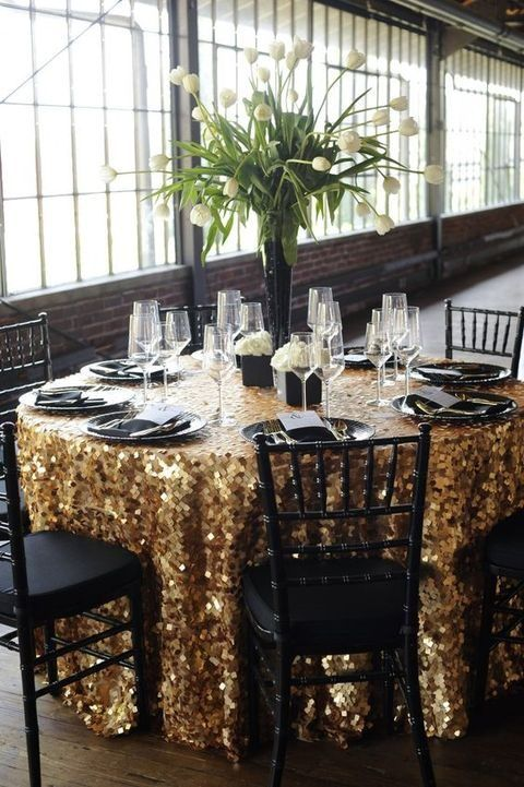 large gold square sequin tablecloth, black plates and vases for a chic New Year's Eve wedding