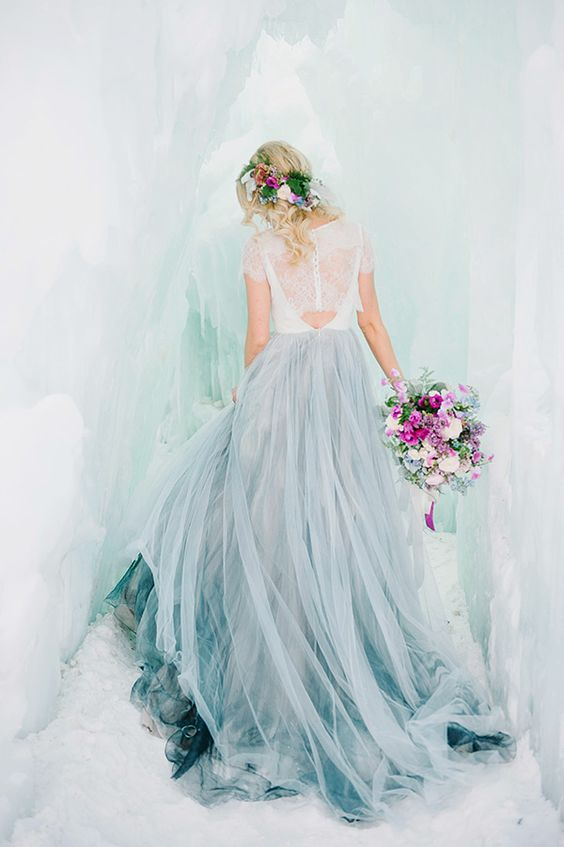 the bride in a lace top, a grey layered skirt in an ice cave