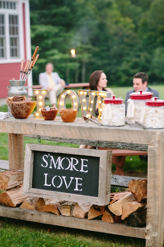 a gorgeous s'mores bar made of a wooden table, with a chalkboard sign and marquee letters