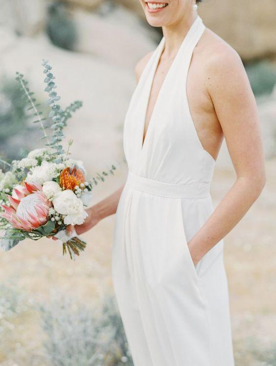 a halter neckline plunging neckline wedding jumpsuit with pockets for a modern bride