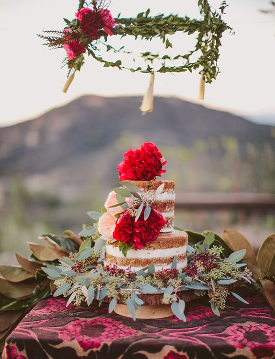 a naked wedding cake with bold red blooms and fresh greenery looks yummy