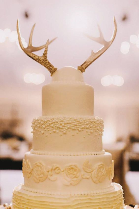a neutral yet textural wedding cake with a gilded antler topper for a woodland wedding