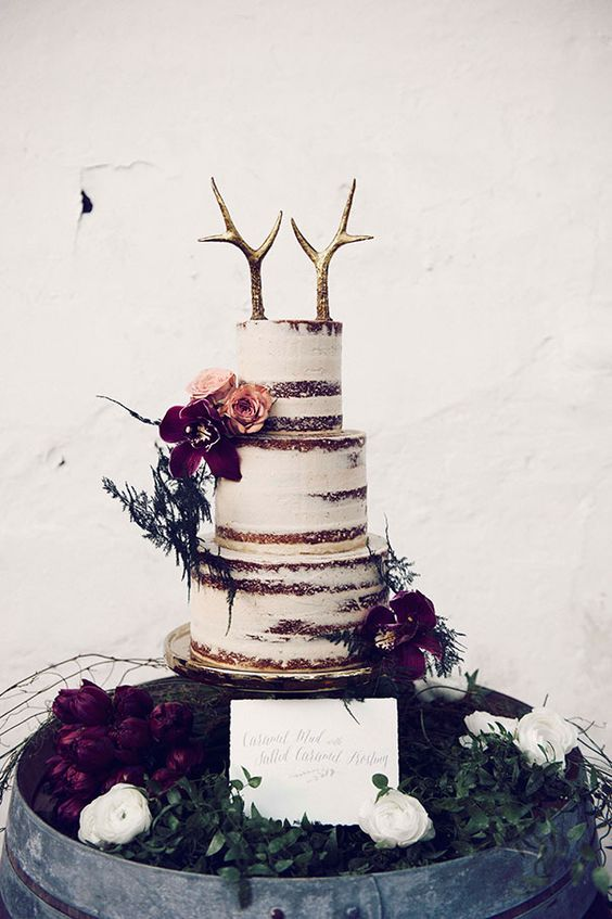 a semi naked wedding cake with gilded antler toppers, burgundy blooms and greenery