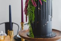 25 a tall matte black wedding cake with chocolate drip, greenery, dark blooms and amaranthus