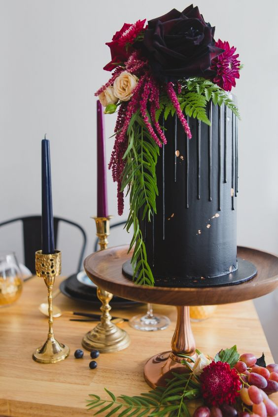 a tall matte black wedding cake with chocolate drip, greenery, dark blooms and amaranthus