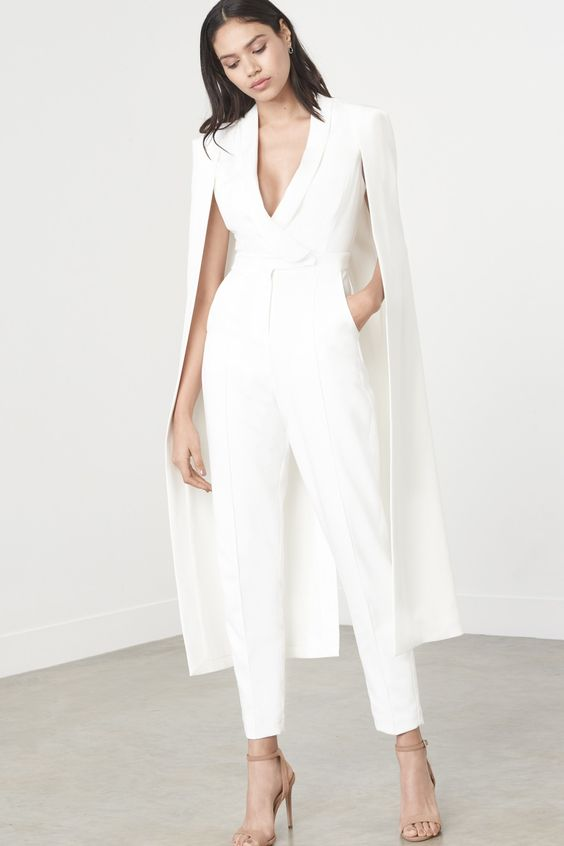 a bridal jumpsuit with a plunging neckline, pockets and a cape attached looks trendy
