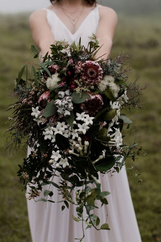 a lush moody winter bouquet with white and moody blooms and lots of greenery