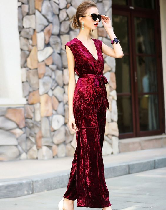 a red velvet belted jumpsuit with no sleeves and a sash is a gorgeous idea that is in trend