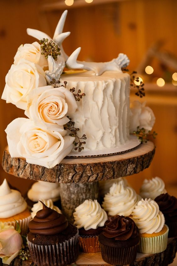 a rustic frosted wedding cake with creamy roses and an antler cake topper
