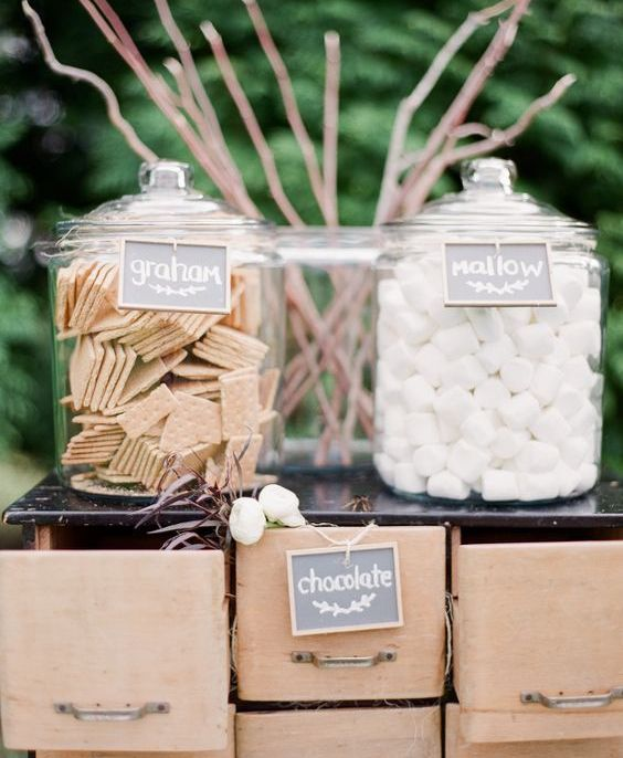 an s'mores station for a farm wedding arranged with sticks, large jars and drawers for storing everything necessary