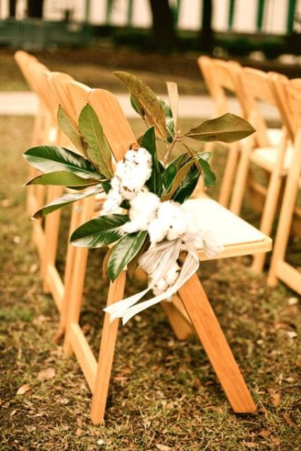decorate the aisle chairs with cotton and magnolia leaves, which is great for a southern wedding