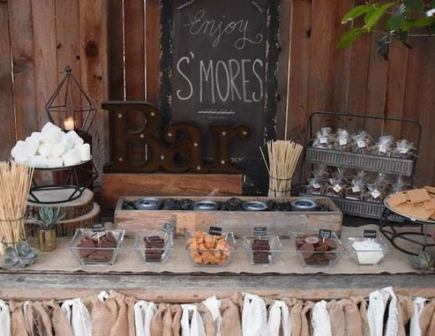 a rustic s'mores bar with a burlap banner, sticks, glass bowls and marquee letters