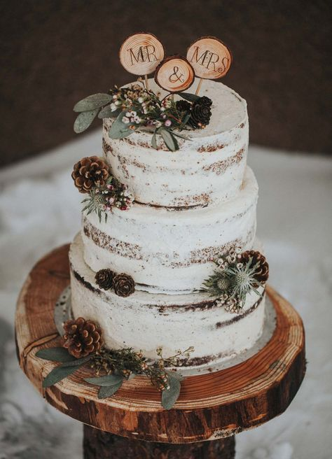 a semi-naked wedding cake with foliage, thistles and pinecones and wood slice toppers