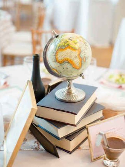 a stack of books with a globe on it for a travel themed wedding