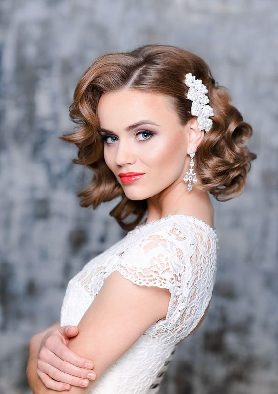 short curly bridal hair with a side pearl hairpiece to make a glam and girlish accent
