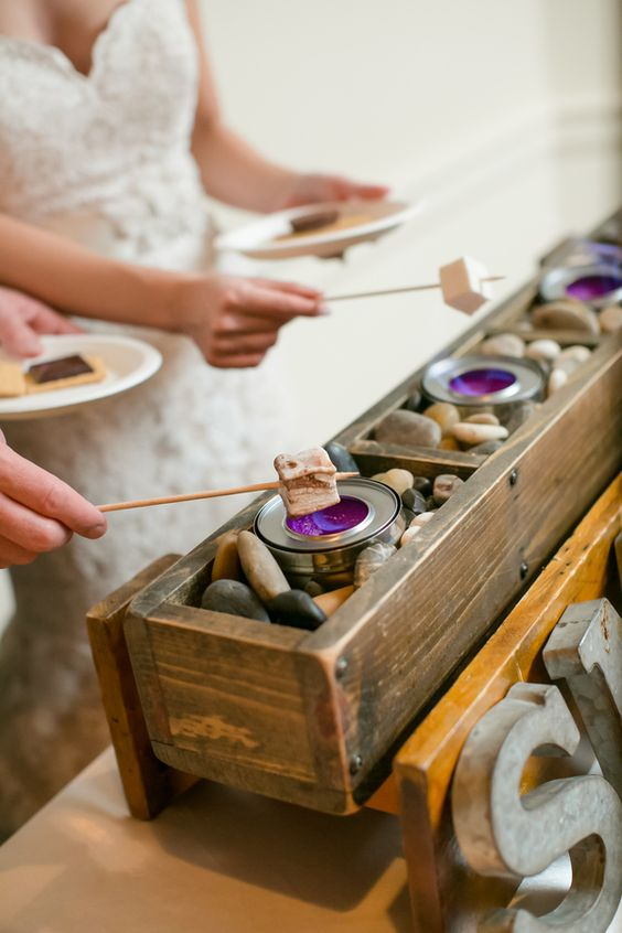 a chic s'more dessert station with wooden boxes and pebbles looks very chic