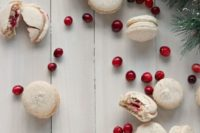 28 orange walnut macarons with spiced cream cheese and cranberry filling for a winter dessert table