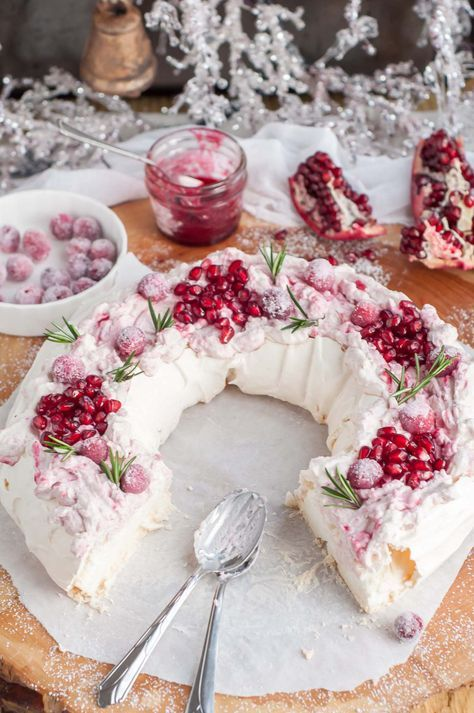 this holiday cranberry and pomegranate pavlova with marshmallowy inside topped with marbled mascarpone cream and berries is a festive paradise