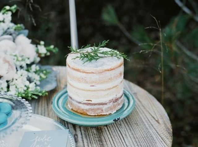 a semi naked wedding cake on an ice blue plate for a winter wedding