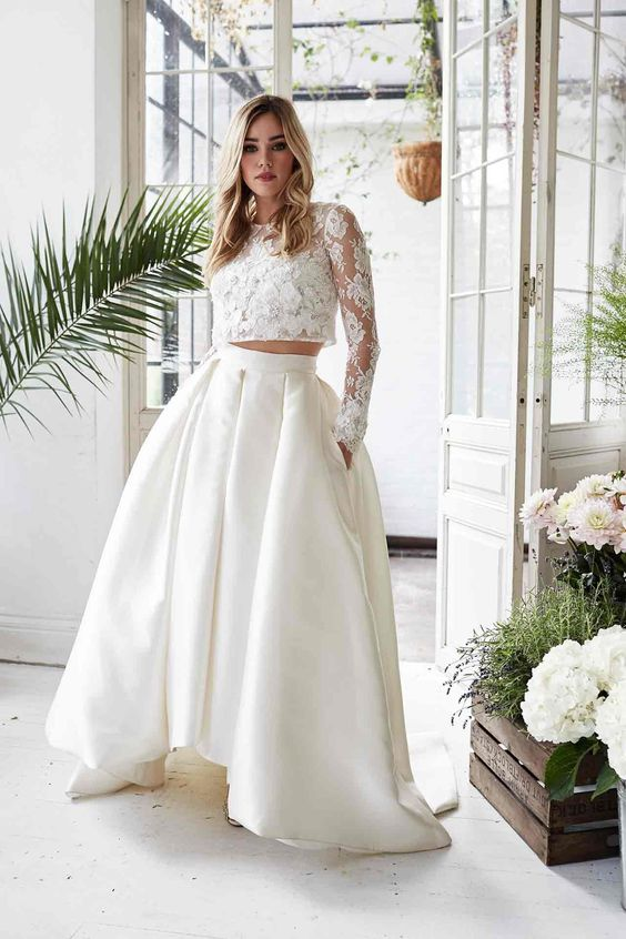a trendy bridal separate with a pleated high low full skirt with pockets and a long sleeve crop top with appliques