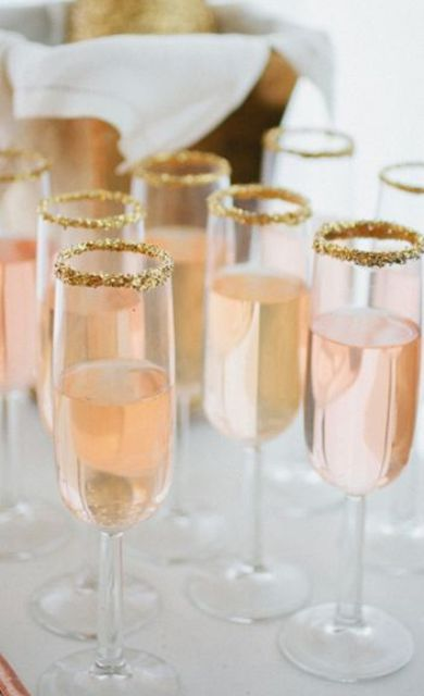 pink champagne in glasses with edible gold glitter edges for a New Year's Eve