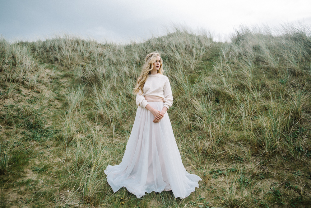 The first bridal look with a flowy skirt and a neutral sweater and a half updo with a braid