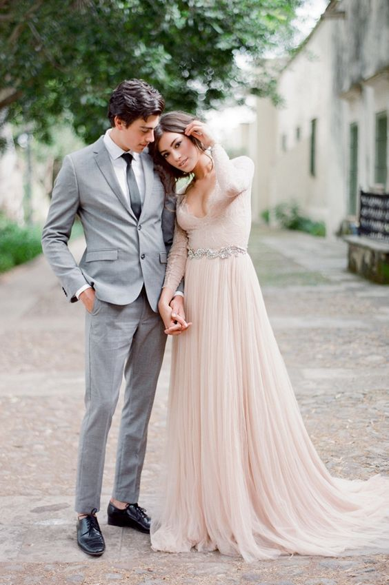 Picture of a blush wedding dress with a plunging neckline long lace picture of a blush wedding dress with a plunging neckline long lace sleeves and an embellished sash junglespirit Image collections