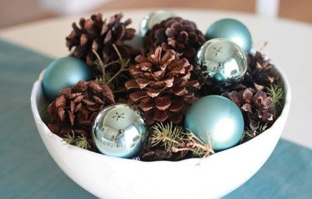 a bowl with pinecones, evergreens and blue and silver ornaments for a winter centerpiece