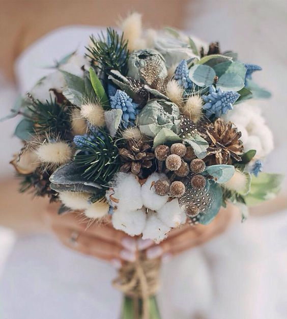 a gorgeous winter bouquet with evergreens, cottons, pinecones and feathers