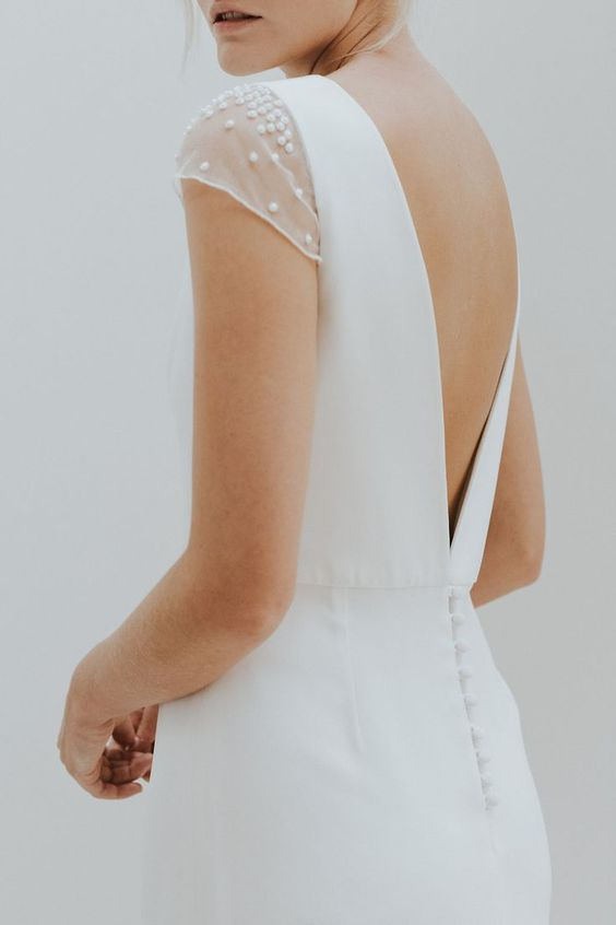 a modern wedding dress with pearly cap sleeves and a V cut back, a row of buttons on the back
