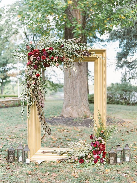 A Refined Backdrop With Large Gilded Frame Lush Greenery And Bold Burgundy Blooms Plus