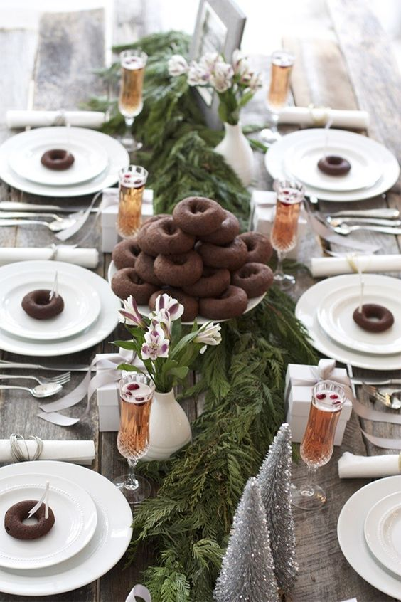 an ultimate tablescape with a fresh greenery runner, silver trees, chocolate donuts to make each place setting