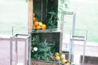 02 venue decor with crates filled with greenery and iranges, large candle lanterns around