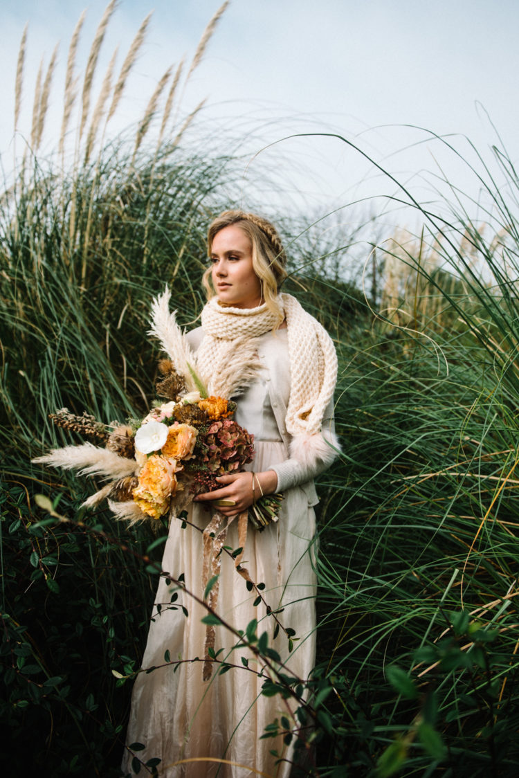 Her second bridal look with a flowy dress and a chunky knit scarf, a fall bouquet