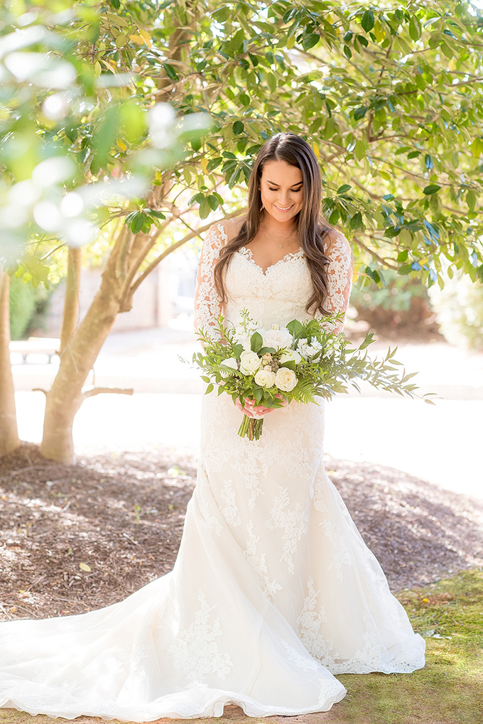 The bride was wearing an illusion neckline wedding dress with lace sleeves and a train