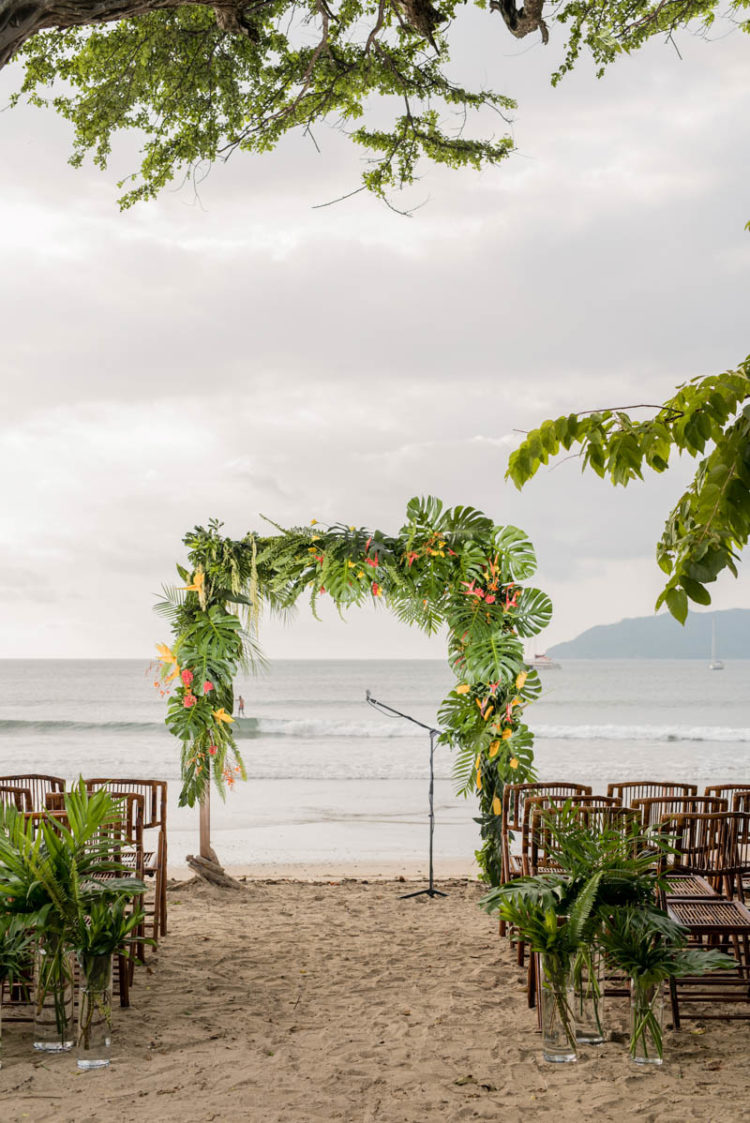 The wedding arch was done with tropical leaves and bold blooms