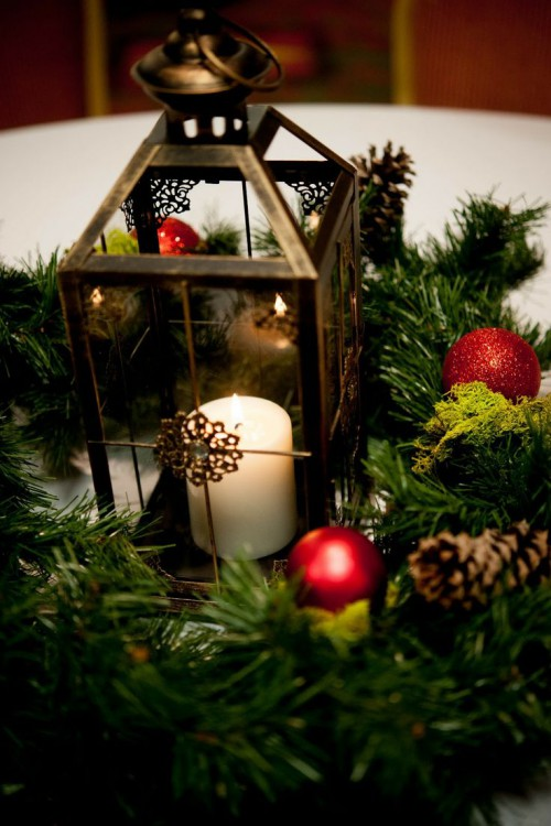a Christmas centerpiece of fir branches, ornaments and a candle lantern in the center