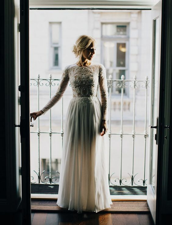 a high neckline long sleeve wedding dress with an embroidered and embellished bodice and a plain skirt