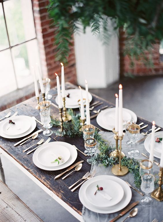 an airy table runner, an evergreen one and gilded candle holders and gold rim glasses