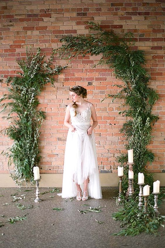 lush greenery attached to a brick wall and candles around look very spectacular and chic
