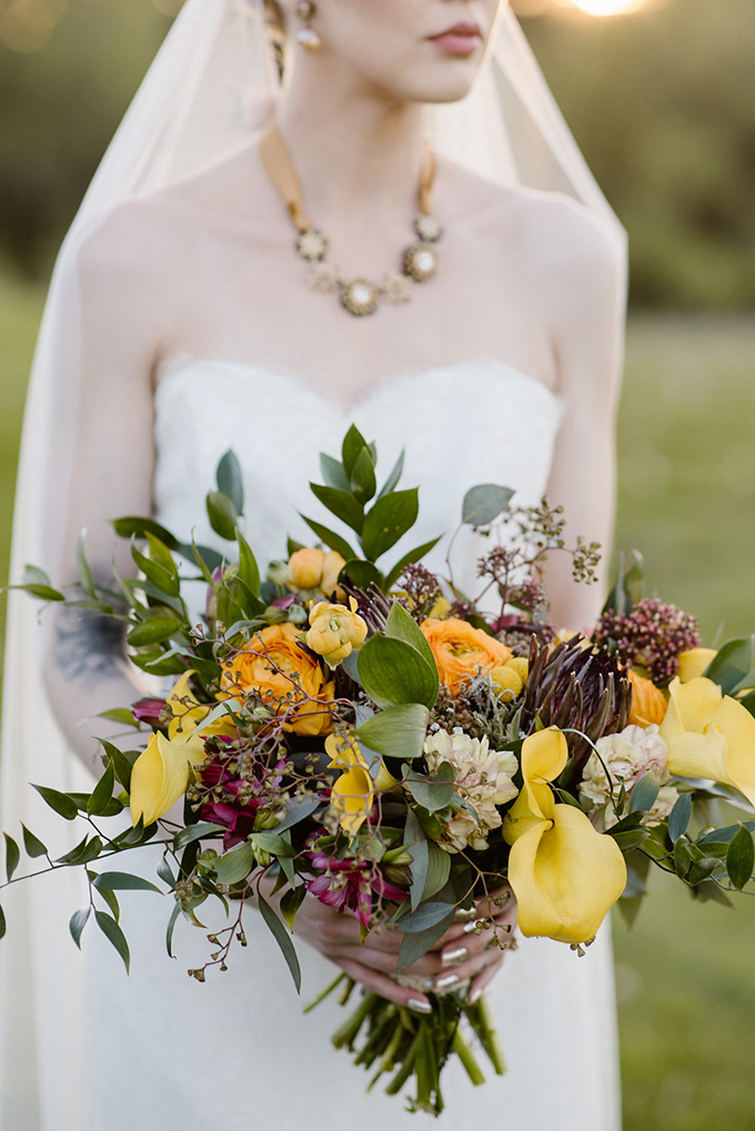 The bridal bouquet is done with mustard blooms, berries and lots of foliage