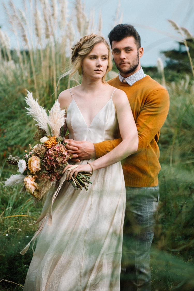 The bride was wearing a spaghetti strap silk wedding dress, the groom was wearing a mustard sweater and grey printed pants