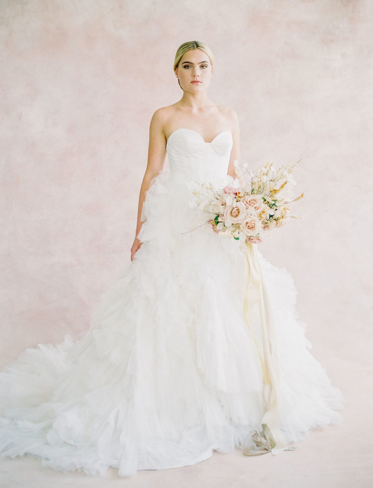 The first bridal look was done with a strapless sweetheart neckline wedding dress with a ruffled skirt