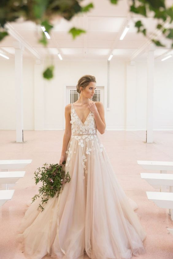 a blush tulle wedding dress with floral appliques on the bodice and a deep V neckline