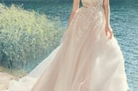 04 a chic blush wedding dress with a lace bodice and a layered skirt with a large train