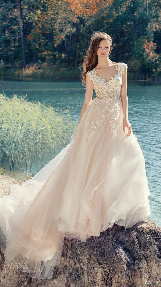 a chic blush wedding dress with a lace bodice and a layered skirt with a large train